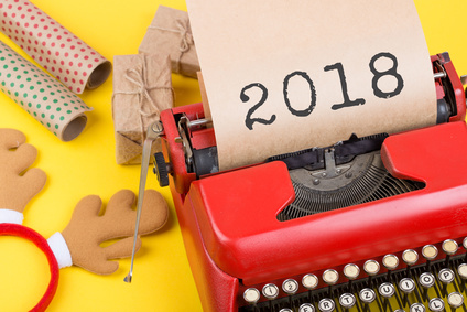 """Christmas concept - typewriter with the text """"2018"""", gift boxes and wrapping paper on yellow background"""